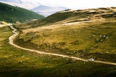 Een mooi Karpatisch landschap met een weg en een auto Stock Afbeeldingen