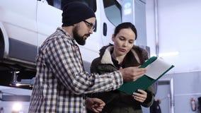 Een mooi-kijkt meisje, een brunette, ondertekent documenten met een werktuigkundige van het autoonderhoud over het ontvangen van  stock footage