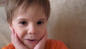 Een mooi kind bekijkt de camera en glimlacht stock footage