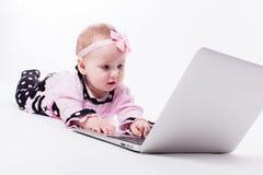 Een mooi klein babymeisje die op haar maag in een slimme speld liggen stock afbeelding