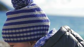 Een mooi klein kind in een de winterhoed, die op het strand met speelgoed spelen stock footage