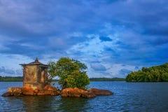 Een mooi landschap van een eiland met bomenstruiken en water en wolk stock afbeelding