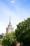 Een mooi lang gebouw, een wolkenkrabber van Stalin op de achtergrond van een deel van de bouw van het hotel van de Oekraïne tegen stock fotografie