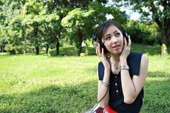 Een mooi meisje dat aan muziek in het park luistert Royalty-vrije Stock Afbeeldingen
