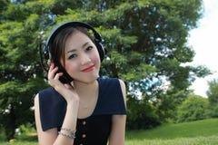 Een mooi meisje dat aan muziek in het park luistert Royalty-vrije Stock Fotografie