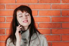 Een mooi meisje die door cellphone, het glimlachen, ogen spreken sloot, met B stock foto