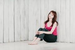 Een mooi meisje die in een roze bovenkant, op de vloer zitten, die op wa leunen royalty-vrije stock fotografie