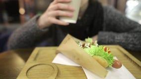 Een mooi meisje drinkt een hete drank met frambozen Een sappige smakelijke hotdog ligt in de voorgrond stock video