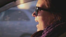 Een mooi meisje in een goede stemming gaat achter het wiel, bij zonsondergang en zingt liederen Langzame Motie stock footage