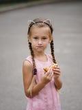 Een mooi meisje eet een cheeseburger op een vage straatachtergrond Een klein meisje met een sandwich royalty-vrije stock afbeeldingen