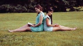 Een Mooi meisje en een leuk meisje zitten op gras rijtjes en lezingsboek en het gebruiken van tablet stock footage