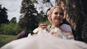 Een mooi meisje en haar vriend zitten onder een boom in het bos op hen zijn glanzend een mooie zon De kerel houdt zijn g stock video