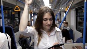 Een mooi meisje gaat naar de metro, houdt de leuning en gebruikt de telefoon stock footage