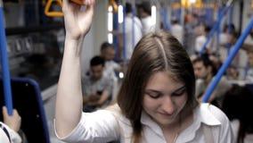 Een mooi meisje gaat naar de metro, houdt de leuning en gebruikt de telefoon stock videobeelden