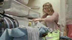 Een mooi meisje is gedeprimeerd, gooit een vermoeide jonge moeder kleren van de manden in haar kleedkamer weg zet stock video