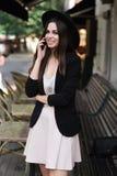 Een mooi meisje gekleed in een modieuze witte kleding, een zwart jasje en een zwarte hoed bevindt zich dichtbij de marmeren koffi stock afbeelding