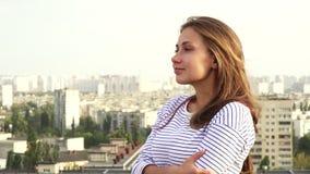Een mooi meisje geniet van ziend van het dak aan de stad royalty-vrije stock foto's