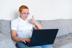 Een mooi meisje in glazen met een rood kader werkt bij laptop Emotie van vreugde met het gebaar van een succesvolle transactie royalty-vrije stock fotografie