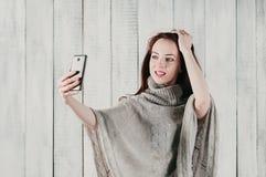 Een mooi meisje in een grijze en trui die, die selfie glimlachen maken royalty-vrije stock foto's