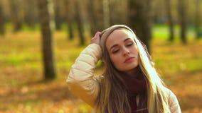 Een mooi meisje, in het de herfstpark, bekijkt de camera en stijgt haar hoed op Het droevige en begin lachen stock video