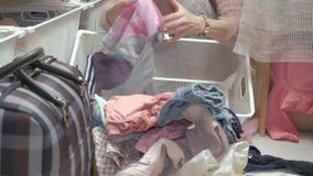 Een mooi meisje, een jonge moeder neemt en vouwt de kleren van kinderen in manden in haar kleedkamer op brengt dingen aan stock footage