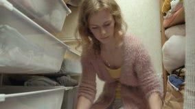 Een mooi meisje, een jonge moeder neemt en vouwt de kleren van kinderen in manden in haar kleedkamer op brengt dingen aan stock video