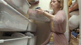 Een mooi meisje, een jonge moeder neemt en vouwt de kleren van kinderen in manden in haar kleedkamer op brengt dingen aan stock videobeelden