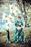 Een mooi meisje in een lange groene kleding bevindt zich in een park naast een reusachtige witte orchidee stock fotografie