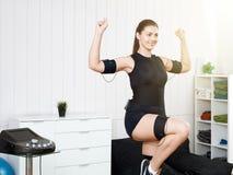 Een mooi meisje leidt in een zwart kostuum op een elektrische simulator van EMS op royalty-vrije stock foto