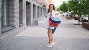Een mooi meisje loopt onderaan de stadsstraat na het winkelen 4K algemeen plan stock footage