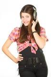 Een mooi meisje luistert muziek in hoofdtelefoons Stock Foto