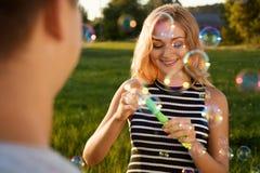 Een mooi meisje met een gelukkige glimlach blazende zeepbels op Stock Foto