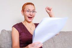Een mooi meisje met glazen met een rood kader las het positieve nieuws in de documenten Emoties van vreugde met het gebaar van a stock afbeeldingen