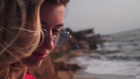 Een mooi meisje met lang blond haar, in een rode T-shirt, in ongebruikelijke, rechthoekige, purpere glazen bekijkt omhoog de zon stock videobeelden