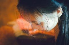 Een mooi meisje met lang donker haar helde haar gezicht over stock fotografie