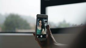 Een mooi meisje met lang zwart haar die een sephi op de telefoon doen stock video