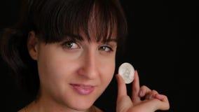 Een mooi meisje met een toekomstige munt, crypto, die het oog behandelen met een muntstuk bitcoin Platinamuntstuk bitcoin stock video