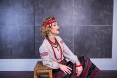 Een mooi meisje in Nationaal Oekraïens Kostuum Gevangen in Studio Borduurwerk en jasje Kroon Circlet van bloemen Rode Lippen Stock Afbeelding
