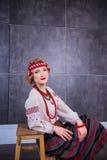 Een mooi meisje in Nationaal Oekraïens Kostuum Gevangen in Studio Borduurwerk en jasje Kroon Circlet van bloemen Rode Lippen Stock Foto