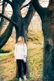 Een mooi meisje in een park met grote bomen stock foto