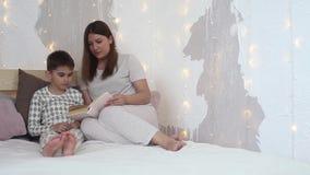 Een mooi meisje in pyjama's leest een boek aan een kleine jongen alvorens naar bed te gaan zitting op het bed algemeen plan stock video