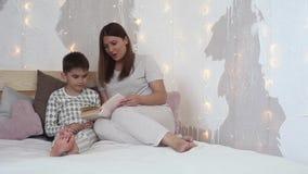 Een mooi meisje in pyjama's leest een boek aan een kleine jongen alvorens naar bed te gaan zitting op het bed algemeen plan HD stock footage