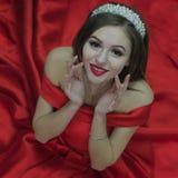 Een mooi meisje in een rode kleding en een wit diadeem zit op de vloer kijkend op en wat betreft haar wangen met haar stock foto
