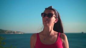 Een mooi meisje in een rood zwempak uit één stuk en glazen bevindt zich op de kust in de stralen van de zonsondergangzon stock video