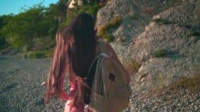 Een mooi meisje in een rood zwempak uit één stuk en glazen loopt langs de kust, op haar schouder een beige rugzak stock footage