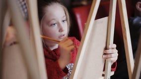 Een mooi meisje schildert een beeld op canvas studio van vroege ontwikkeling Art Studio stock footage