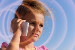 Een mooi meisje spreekt door smartphone, loensend in zonneschijn op blauwe hemelachtergrond Smartphon is Zonsondergang 2 van loop Stock Foto's