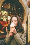 Een mooi meisje in een warm jasje eet trdelnik of Trdlo met room in haar handen, in de winter in de Tsjechische Republiek, Praag  stock foto's