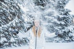 Een mooi meisje werpt sneeuw op een bosopen plek onder de grote bomen royalty-vrije stock afbeeldingen