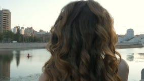 Een mooi meisje in witte kleren ontmoet de dageraad op de stadsdijk Vroege ochtend, mooie dag stock video